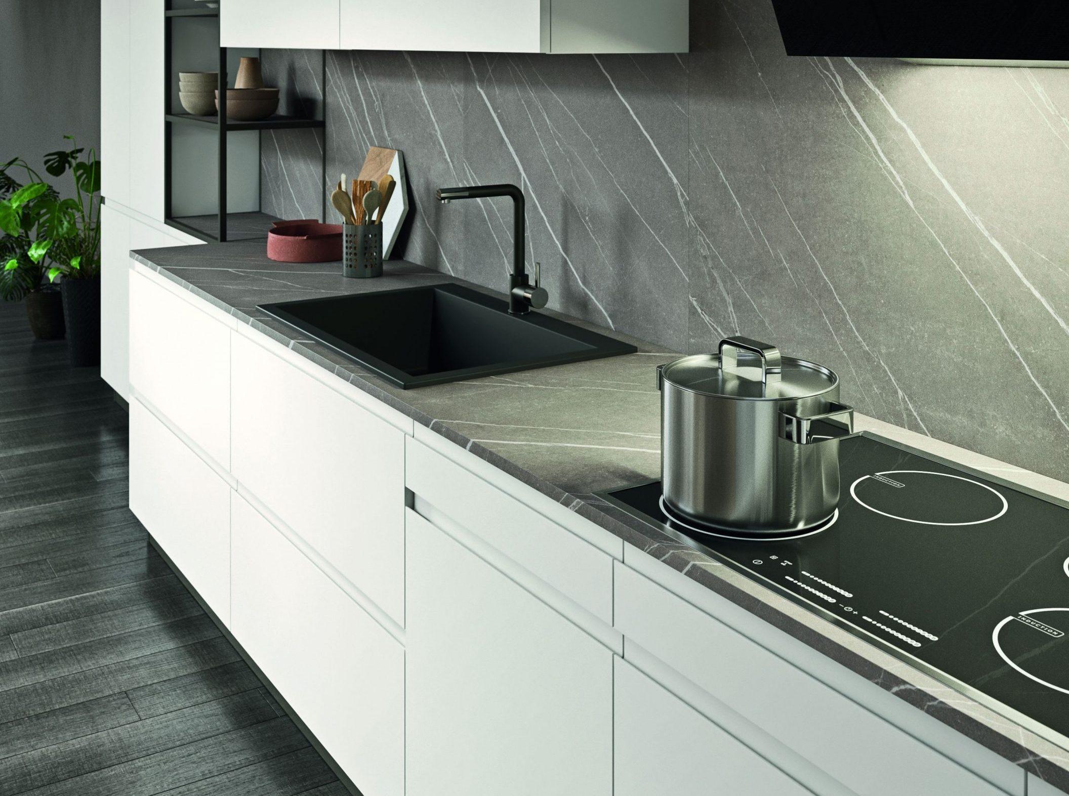 Piano cottura e lavello dello stesso colore del piano in una cucina bianca laccata .