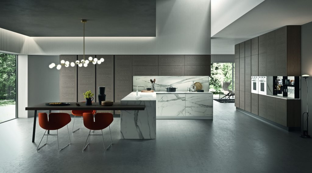 raffinata cucina open space con elementi in finitura bianco venato e colonne in legno decapè tortora che si apre verso l'ampia zona giorno adiacente