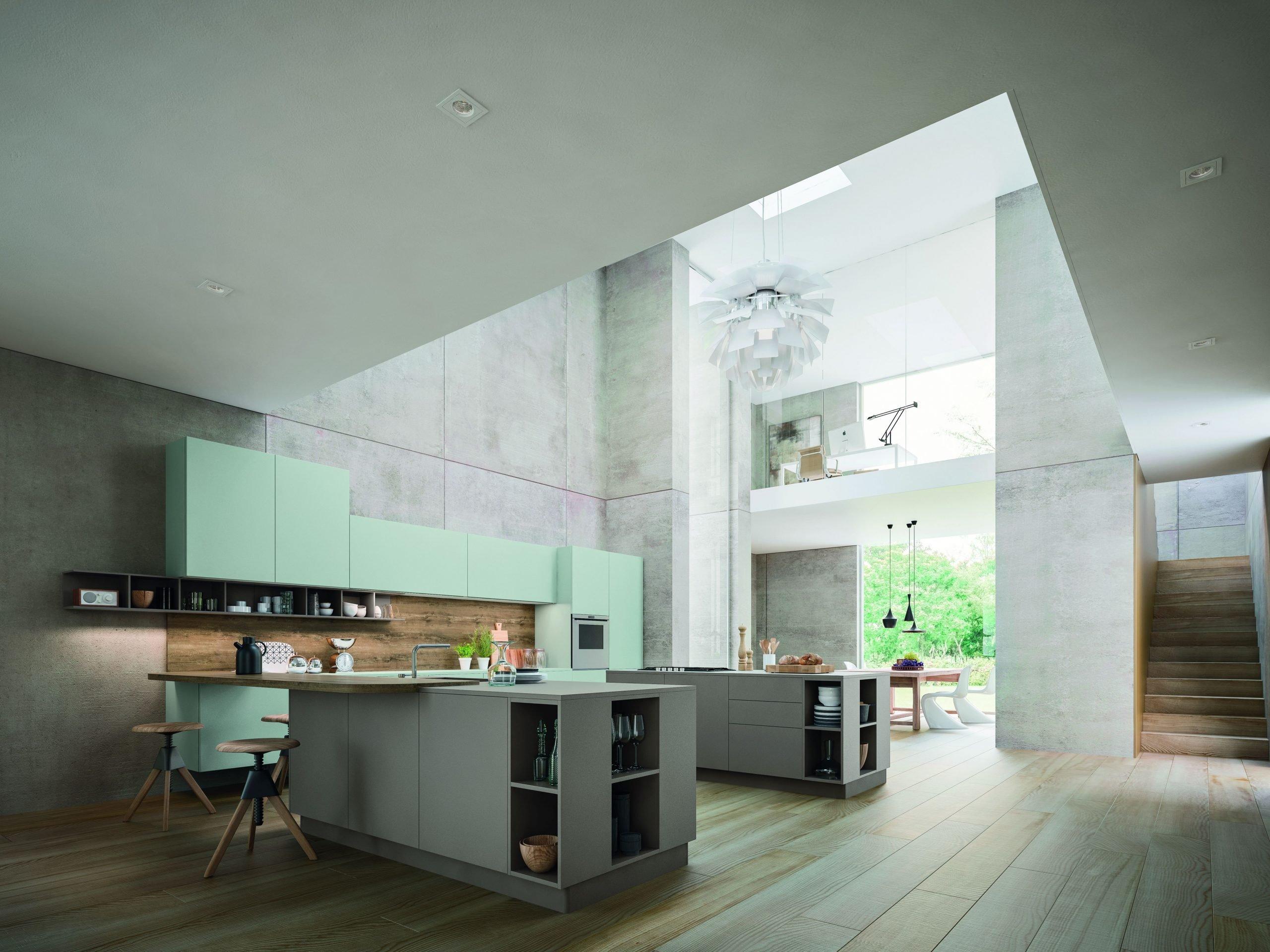 splendida ambientazione di cucina open space colore tortora e verde con vista su area pranzo e soppalco adibito a studio