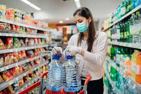 Signora che ripone nel carrello del supermercato bottiglie bere l'acqua in cucina