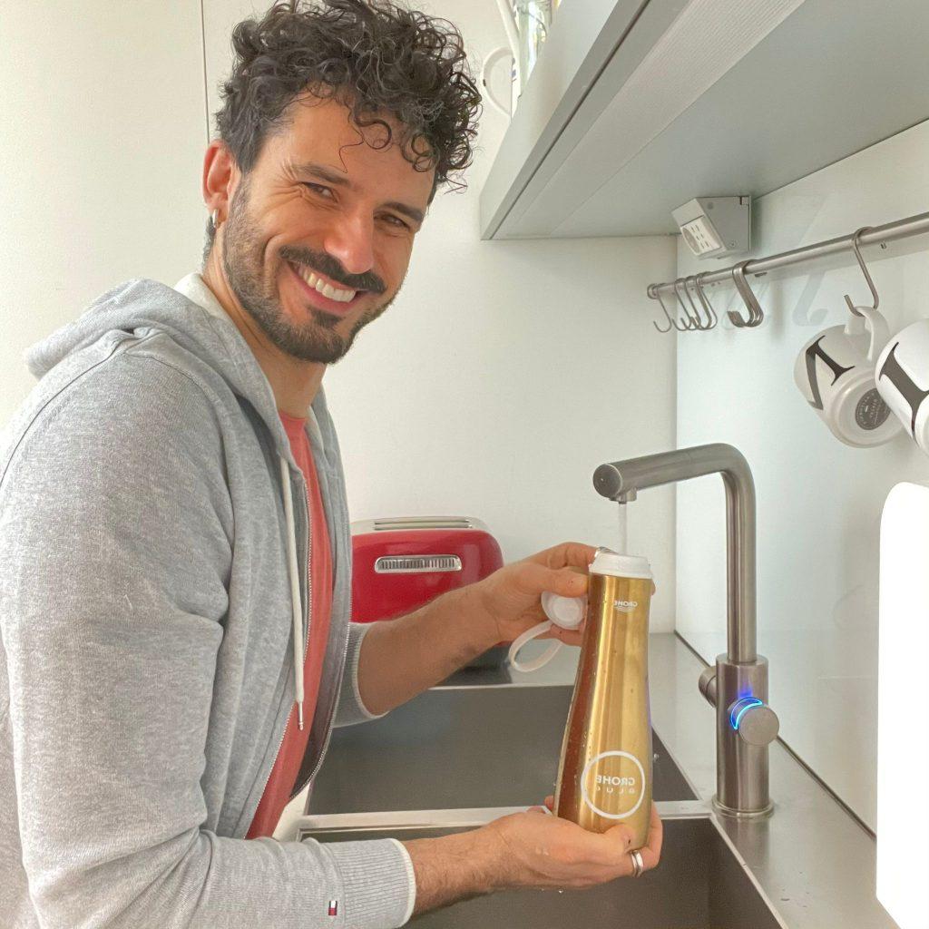 Marco Bianchi noto food mentor riempie la bottiglia d'acqua in cucina dal rubinetto